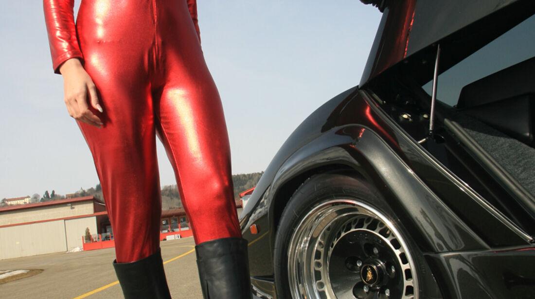 Blondine im roten Catsuit neben Lamborghini Countach Turbo S